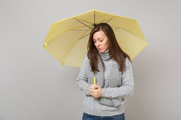 Расстроенная молодая женщина в сером свитере, шарфе, смотрящем вниз, держа желтый зонтик, изолированный на сером фоне в студии. здоровый образ жизни моды, концепция холодного сезона эмоций людей. копируйте пространство для копирования.