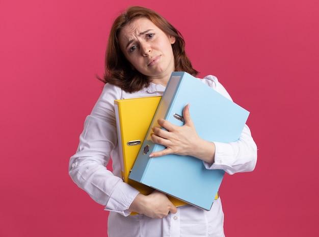 ピンクの壁の上に立っている悲しい表情で正面を見てフォルダーを保持している白いシャツで動揺した若い女性