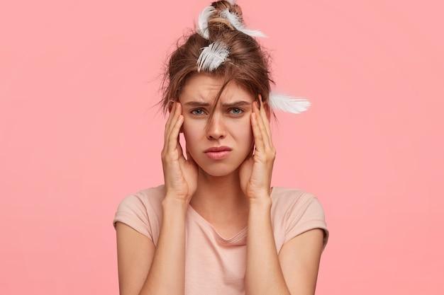Расстроенная молодая женщина держит руки на висках, страдает головной болью, недовольно хмурится, плохо спит ночью, одетая в повседневную футболку