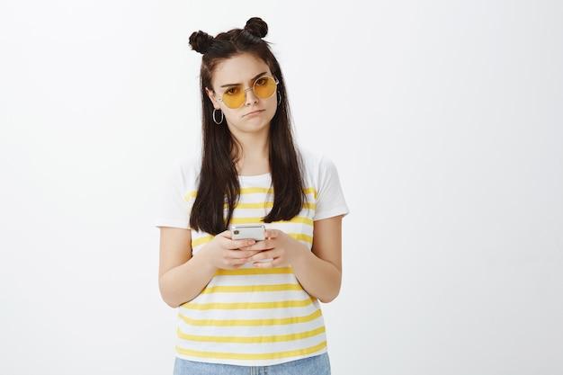 흰 벽에 선글라스와 전화 포즈 화가 젊은 여자