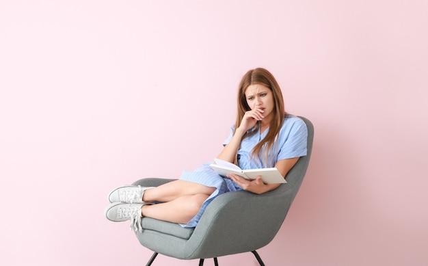 色の本を読んで動揺している若い女性