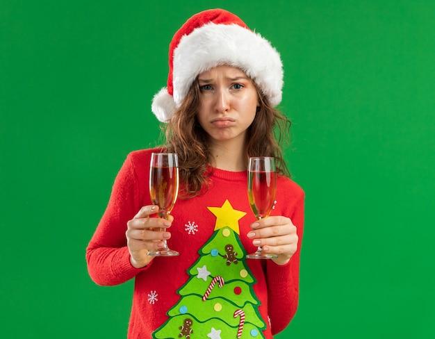 Sconvolto giovane donna in rosso maglione di natale e santa hat tenendo due bicchieri di champagne che guarda l'obbiettivo con espressione triste che porta le labbra in piedi su sfondo verde