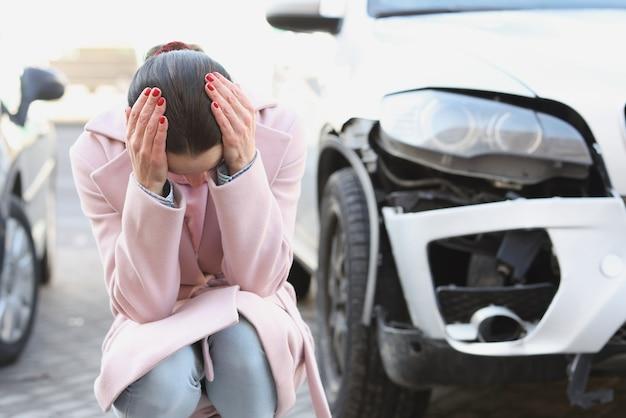 動揺した若い女性は、大破した自動車事故とその結果の隣に頭を下げて座っています