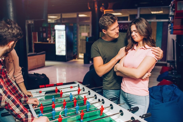 Upset young woman stand at tabel soccer in playing room. guy try to comfort her and embrace. they stand in front another couple.