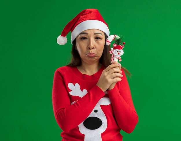 Sconvolto giovane donna che indossa il natale santa cappello e maglione rosso tenendo il natale candy cane guardando la telecamera con espressione triste che porta le labbra in piedi su sfondo verde
