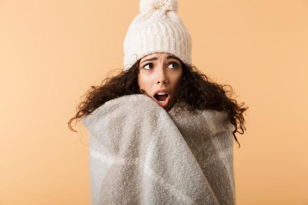 Расстроенная молодая женщина в зимнем шарфе стоит изолированно над бежевой стеной и дрожит