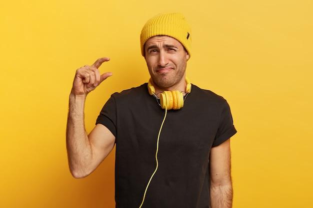 Il giovane sconvolto mostra piccole dimensioni con le dita, mostra misure minuscole, sorride in faccia, racconta la diminuzione delle vendite