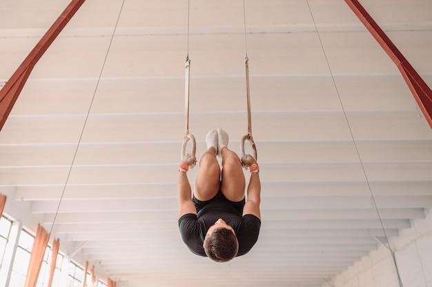 Перевёрнутый человек тренируется на гимнастических кольцах
