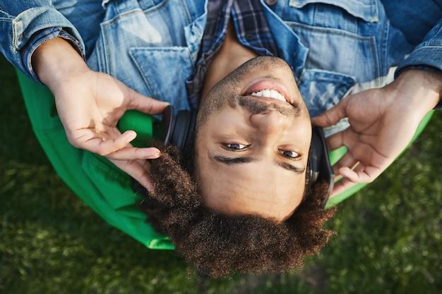 Capovolto ritratto di felice giovane sportivo afro-americano sdraiato nel parco sulla sedia sacchetto di fagioli verdi, sorridendo alla telecamera mentre si tengono le cuffie sulle orecchie e ascoltando musica.
