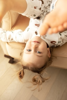 Перевёрнутый портрет симпатичной активной эмоциональной очаровательной детской девочки, лежащей вверх ногами на biege chear и развлекающейся в помещении