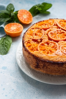 Upside down tangerine cake on a sky-blue stone or concrete background.