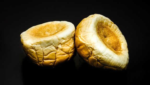 Upside down two delicious burger buns on a textured dark background