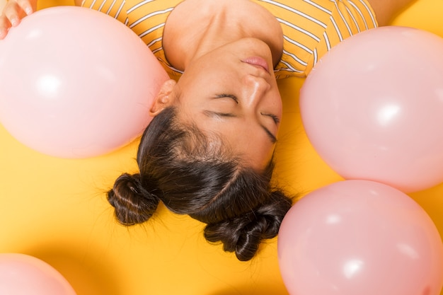 Upside down woman surrounded by balloons