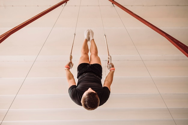 Перевернутый молодой человек тренируется на гимнастических кольцах