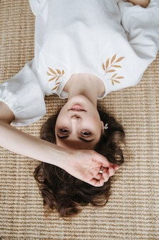 Upside portrait of a beautiful young woman in summer dress with leaf pattern lying on the floor inside a room. pretty brunette with short hair indoors.