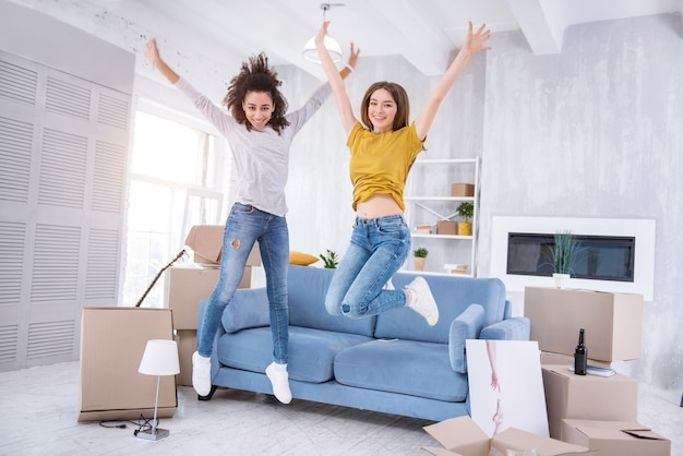 Всплеск эмоций. приятные жизнерадостные девушки радостно прыгают в новой квартире, вместе празднуя переезд в новую общую квартиру