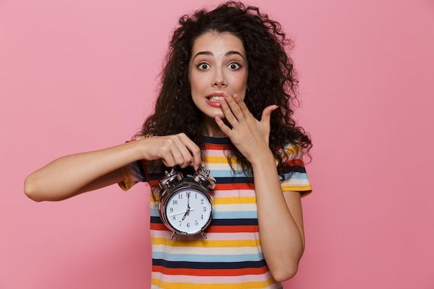 ピンクで隔離の目覚まし時計を保持している巻き毛の20代の緊張した女性