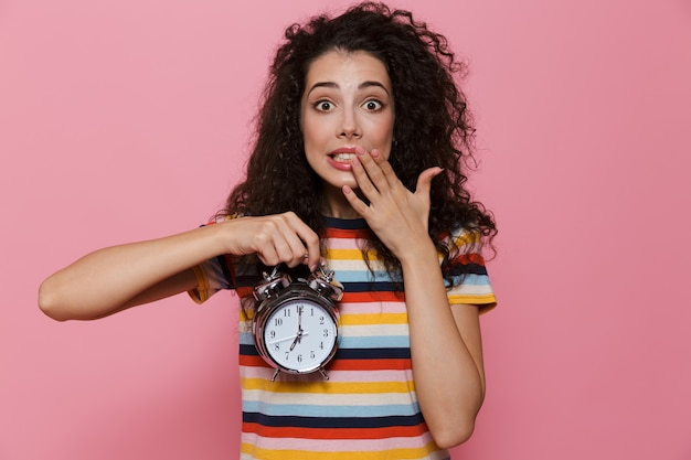 Uptight woman 20s with curly hair holding alarm clock isolated on pink