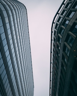 Upward vertical of modern tall business buildings with a white sky