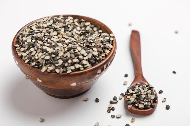 黒いレンズ豆としても知られている黒いグラム、黒いurad dal、vigna mungo、白い背景の上椀のurad豆