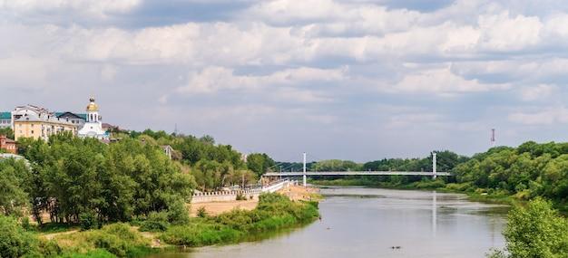川の遊歩道のビーチと橋のある夏の街並みのウラル川