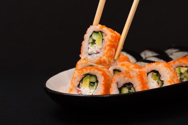カリフォルニア州裏巻き。海苔、ご飯、アボカド、きゅうり、黒の背景のセラミックプレートに飛んでいる魚の卵で飾られた巻き寿司。