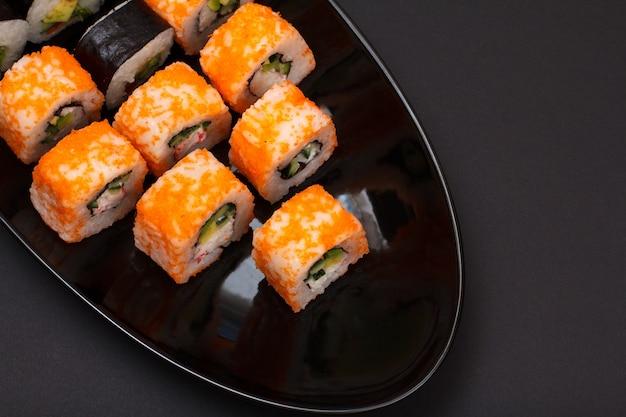 Урамаки калифорния. суши-роллы с нори, рисом, кусочками авокадо, огурцом, украшенные икрой летучей рыбы на керамической тарелке. вид сверху. черный фон.