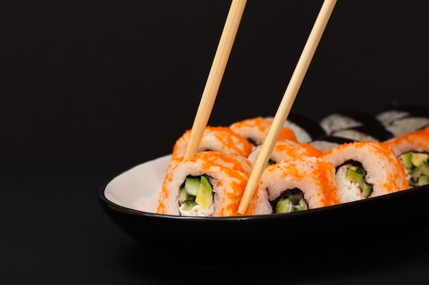Урамаки калифорния. суши-роллы с нори, рисом, кусочками авокадо, огурцом, украшенные икрой летучей рыбы на керамической тарелке с деревянными палочками.