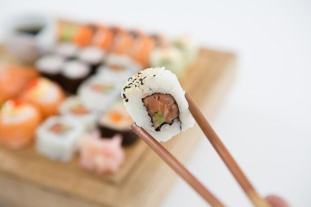 Uramaki sushi being held in wooden chopsticks