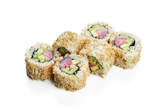 Урамаки суши ролл калифорния в кунжуте с тунцом, авокадо и огурцом. классическая японская кухня. доставка еды. изолированные на белом.
