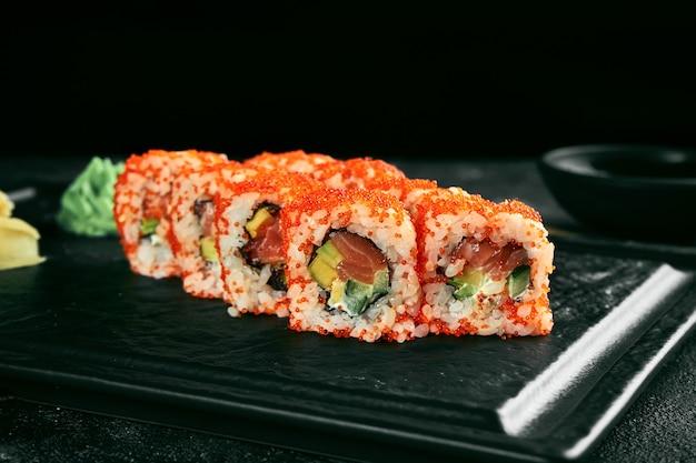 Урамаки суши калифорнийский ролл в икре тобико с лососем, авокадо и огурцом. классическая японская кухня. доставка еды.