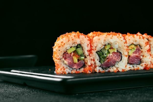 Урамаки суши калифорнийский ролл в икре тобико с тунцом, авокадо и огурцом. классическая японская кухня. доставка еды. изолированные на белом.