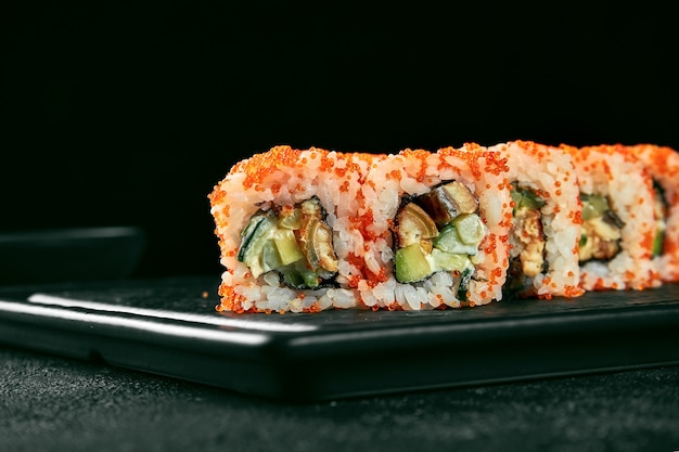 Uramaki sushi california roll in tobiko caviar with eel, avocado and cucumber. classic japanese cuisine. food delivery. isolated on white.