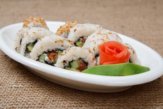 裏巻き寿司は、赤い魚と生姜のピクルス、白い磁器の皿にアボカド、荒布に木の棒が付いています。