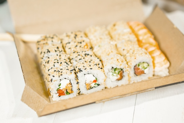 Uramaki sushi rolls with sesame inside a brown paper package.