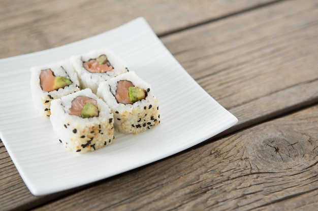 Uramaki sushi served on plate against wooden table