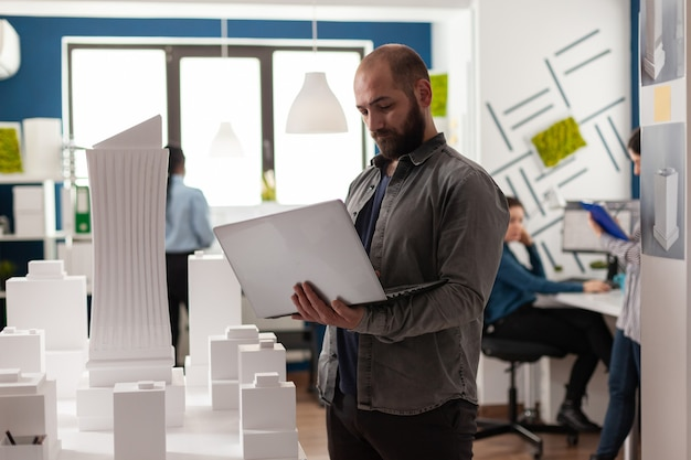 Urban adult architect inspecting design plan at workplace