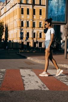 都市通りの広場を歩いて都市アフロアメリカンの女性