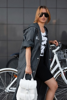세련된 배낭 티셔츠에 긴 재킷에 어두운 선글라스에 도시 미국 현대 젊은 여성이 자전거 주차장 근처의 도시에서 야외에서 포즈를 취합니다. 산책에 유행 소녀입니다.