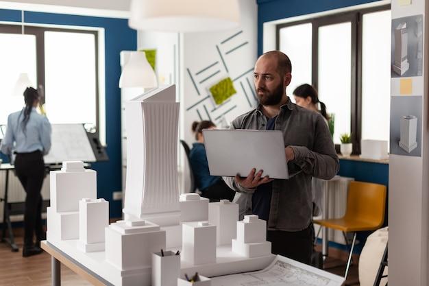 전문적인 레이아웃을 위해 직장에서 설계 계획을 검사하는 도시 건축가 성인