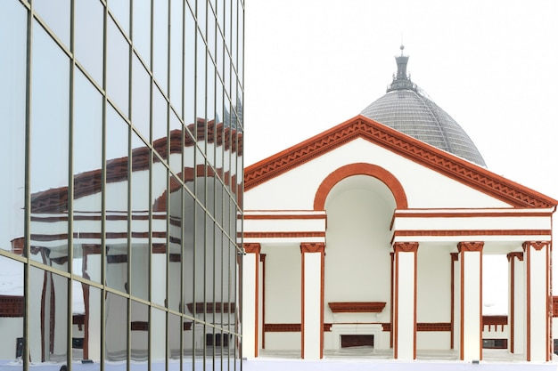 도시 건축은 스타일이 혼합 된 건물입니다. 20 세기 초의 스타일로 건물의 유리 외관에 반사. 현대 도시에서 다양한 스타일의 건축 시연.