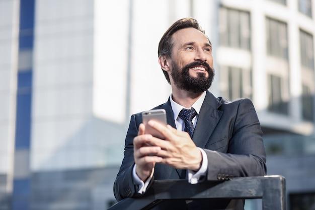 都市建築。笑顔で彼の携帯電話を保持している陽気なハンサムなビジネスマンの腰
