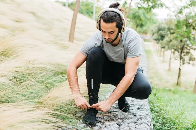 Urban athlete fastening his shoes