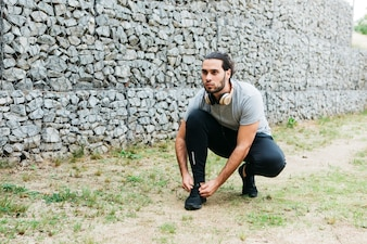 Urban athlete fastening shoes
