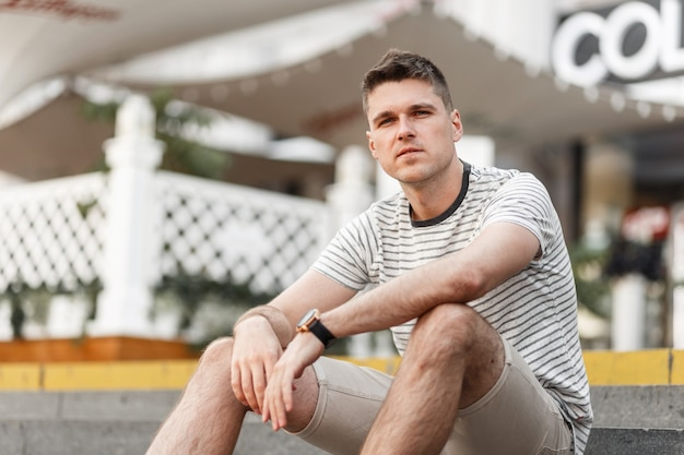 Urban attractive young man in a fashionable t-shirt in beige stylish shorts is resting sitting on the steps in the city.