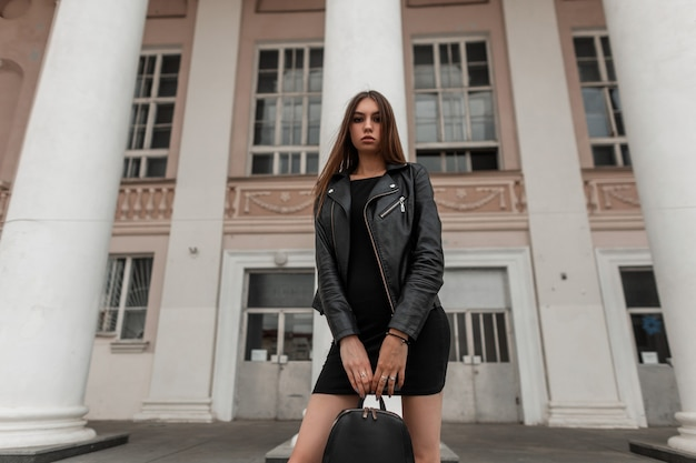 Urban attractive young woman with brown hair with in a leather stylish jacket in a black dress with a black fashionable bag standing near a vintage building with columns. girl walks around the city.