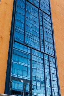 도시 배경 - 다른 건물을 반영하는 유약이 있는 정면의 조각
