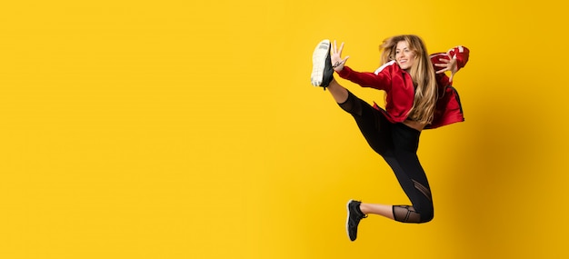 Urban ballerina dancing over isolated yellow background and jumping
