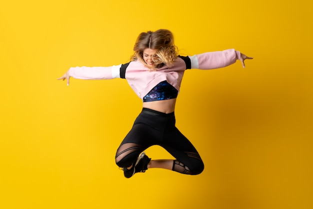 Urban ballerina dancing over isolated yellow  and jumping