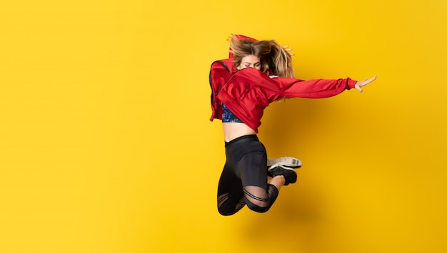 Urban ballerina dancing over isolated yellow wall and jumping